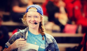 Sarah wearing backwards hat, a FIRST volunteer shirt, and microphone at a FIRST event.