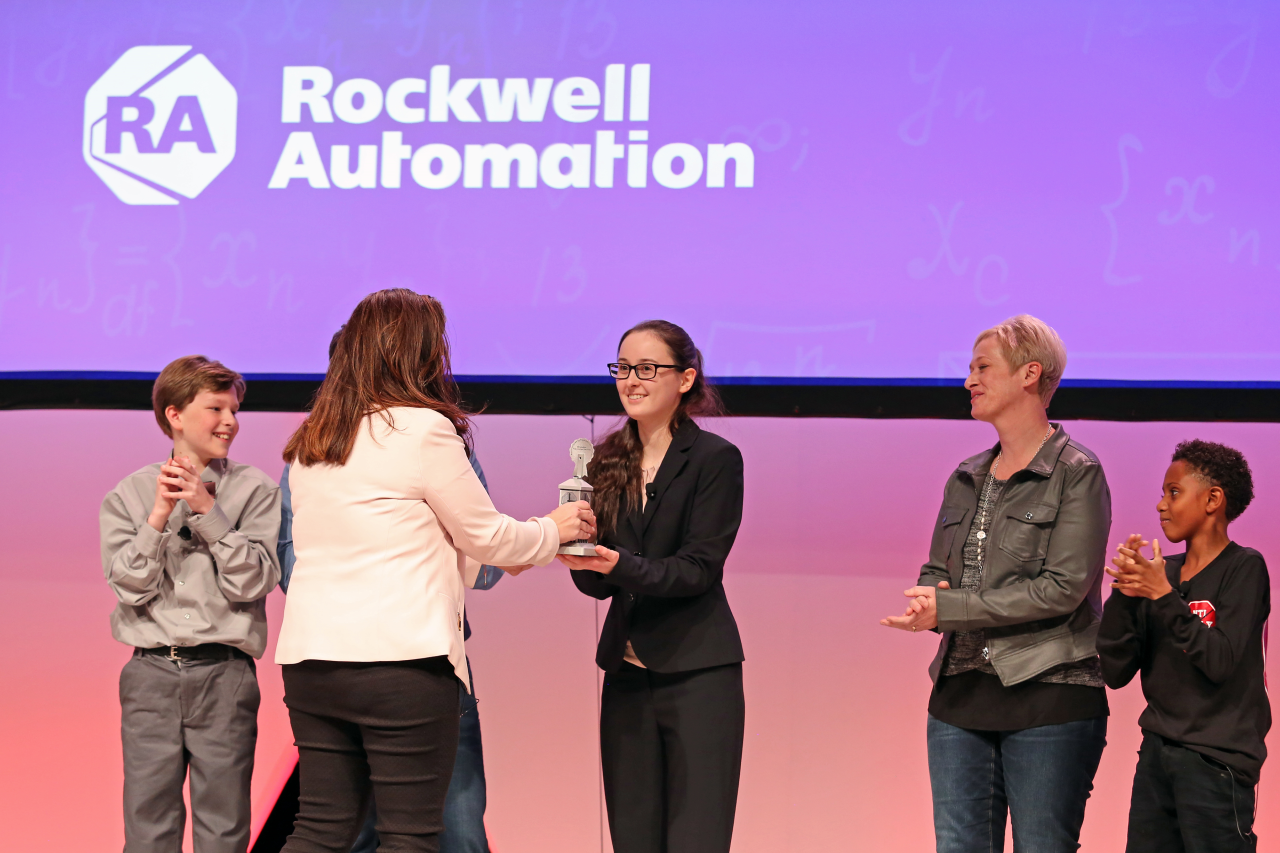 FIRST participant Louisa Wood accepts her trophy as winner of Rockwell Automation's You Make It Challenge.